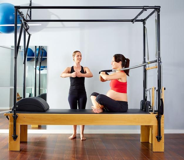 Mulher grávida pilates reformer braços exercício
