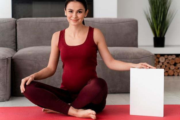 Mulher grávida posando ao lado de um cartão branco