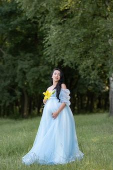Mulher grávida posando com um vestido azul com árvores verdes.
