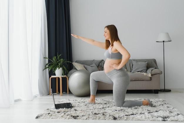 Mulher grávida praticando ioga em casa com o laptop. mãe grávida fazendo aula de treinamento em vídeo pré-natal dentro de casa. exercícios femininos, medite durante a gravidez. aula de fitness online em dispositivos digitais.