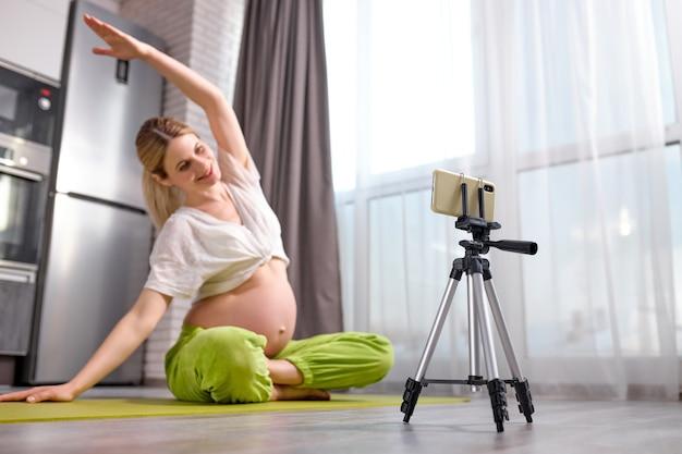 Mulher grávida praticando ioga em casa com uma futura mãe no smartphone, fazendo aula de treinamento em vídeo pré-natal