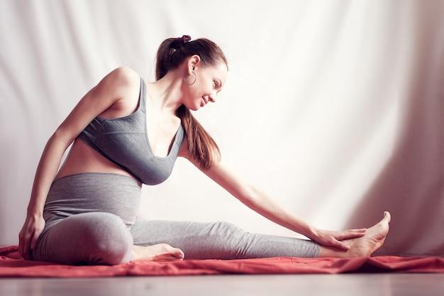 Mulher grávida praticando ioga em casa.