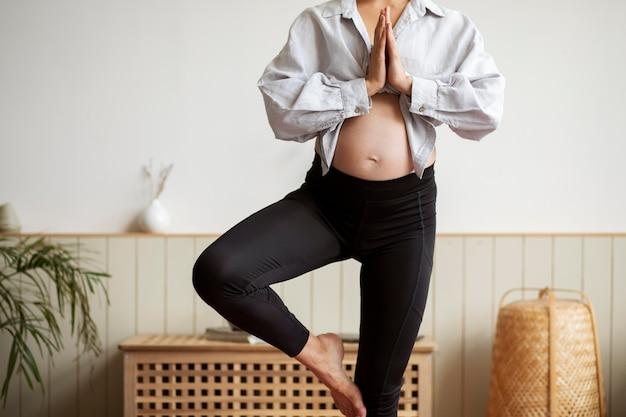 Mulher grávida praticando ioga em casa