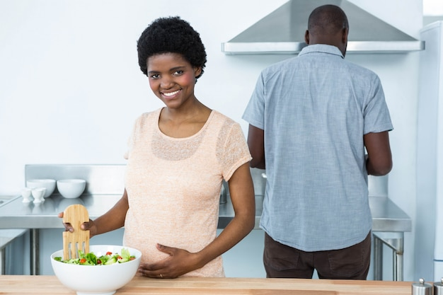 Mulher grávida preparando salada e homem trabalhando atrás dela na cozinha
