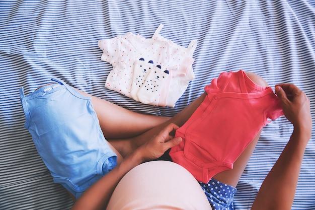 Mulher grávida procurando roupas de bebê. jovem mãe à espera de um bebê.