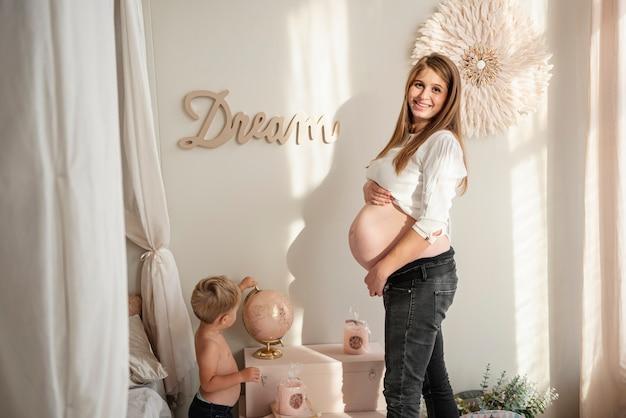 Mulher gravida que está com seu filho em um quarto dentro de casa