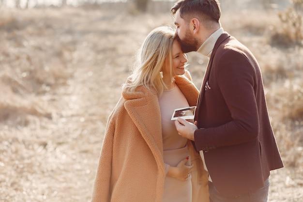 Mulher gravida que está em um parque com seu marido