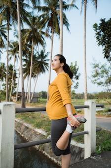 Mulher gravida que exercita ao ar livre