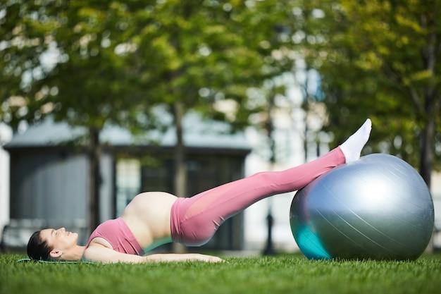 Mulher gravida que exercita com a bola no parque