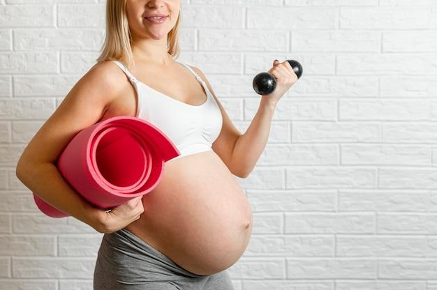 Mulher gravida que faz o exercício da aptidão