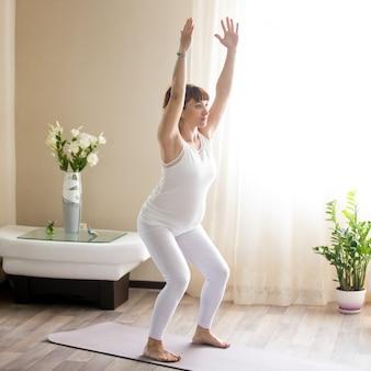 Mulher grávida que faz utkatasana, cadeira yoga pose em casa