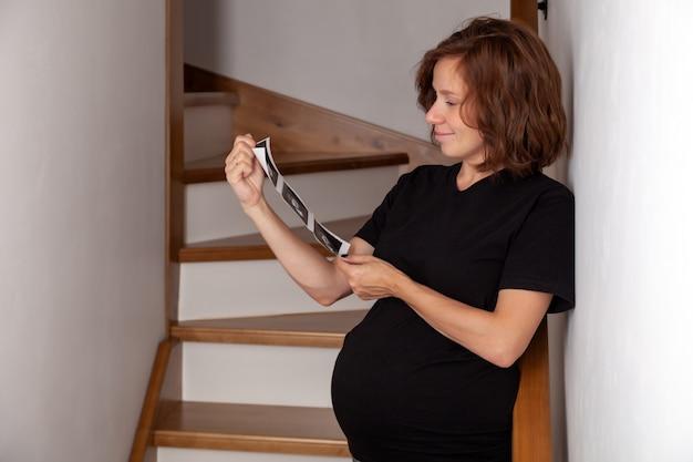 Mulher gravida que olha sua ecografia do bebê