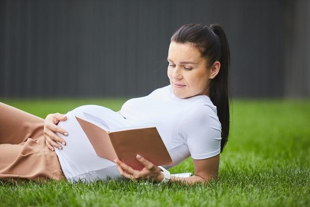 Mulher gravida que relaxa com livro