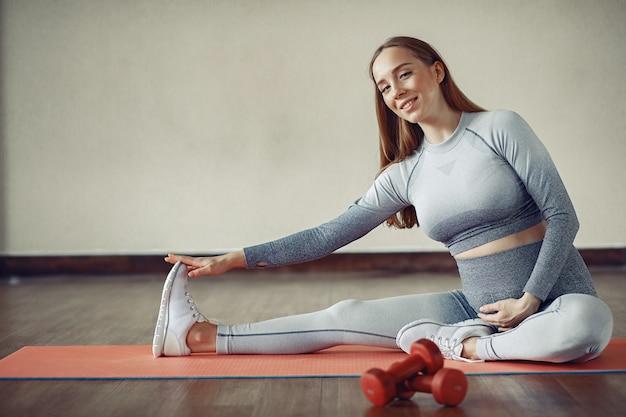 Mulher gravida que treina em uma academia