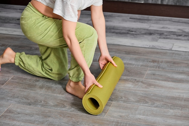 Mulher grávida recortada desenrola o tapete de fitness antes do treino
