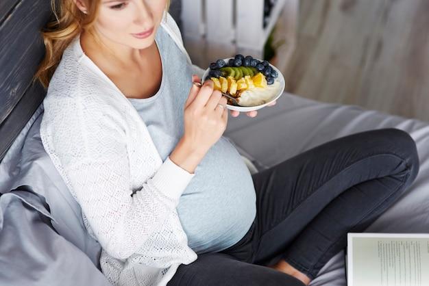 Mulher grávida relaxando em casa
