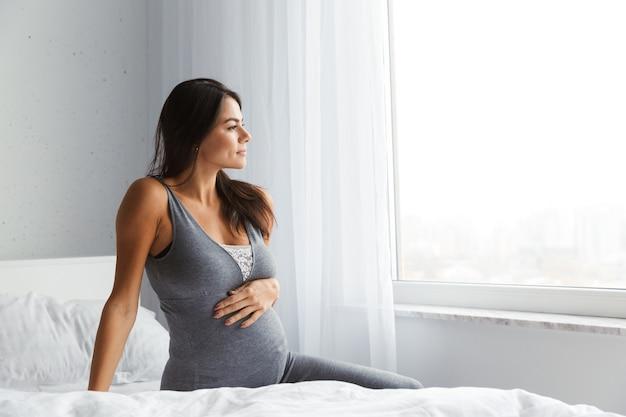 Mulher grávida saudável dentro de casa em casa sentada posando.