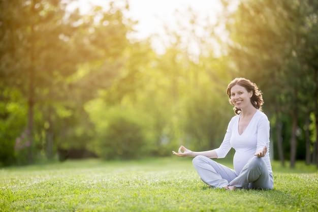 Mulher grávida saudável na sessão de meditação sobre a localização da natureza