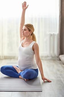 Mulher grávida saudável sentada no chão, levantando as mãos, fazendo exercícios