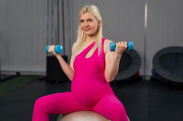 Mulher grávida se exercita com halteres na bola de fitness na academia.
