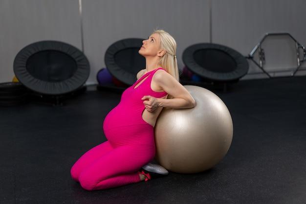 Mulher grávida se exercita com uma bola de fitness na academia.