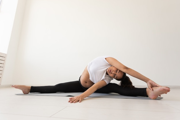 Mulher grávida se exercita propositalmente durante a aula de ioga e relaxa enquanto está sentada em uma esteira
