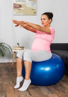 Mulher grávida se exercitando em casa com bola