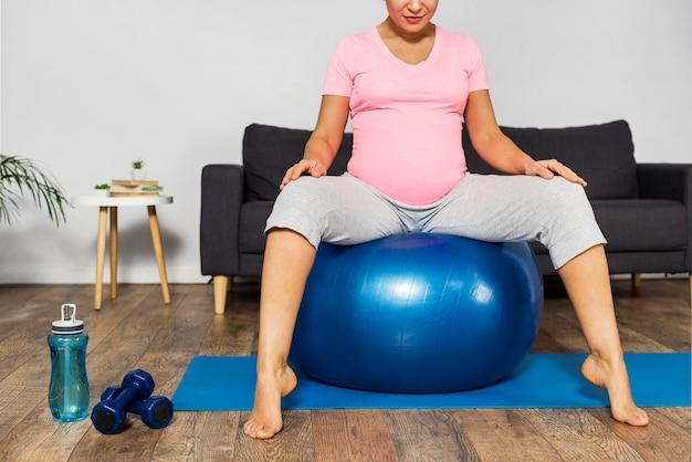 Mulher grávida se exercitando em casa no chão com bola e garrafa d'água