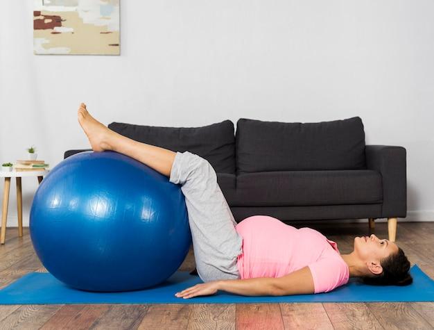 Mulher grávida se exercitando em casa no chão com bola