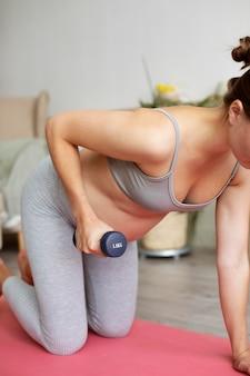 Mulher grávida se exercitando em casa