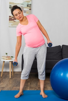 Mulher grávida se exercitando no colchonete em casa com bola e pesos