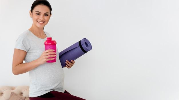 Mulher grávida se preparando para se exercitar com espaço de cópia