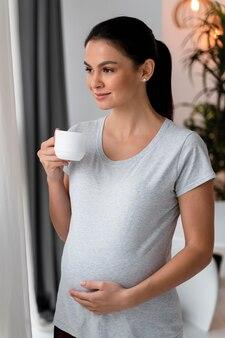 Mulher grávida segurando a barriga enquanto toma uma xícara de chá