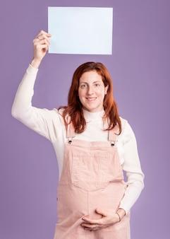 Mulher grávida segurando a folha de papel em branco