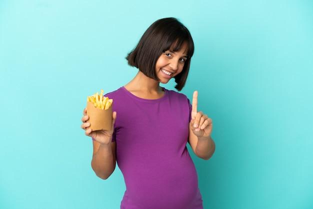 Mulher grávida segurando batatas fritas sobre fundo isolado, mostrando e levantando um dedo