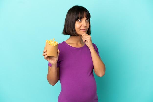 Mulher grávida segurando batatas fritas sobre fundo isolado, tendo dúvidas e pensando