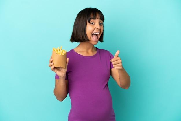 Mulher grávida segurando batatas fritas sobre um fundo isolado com o polegar levantado porque algo bom aconteceu