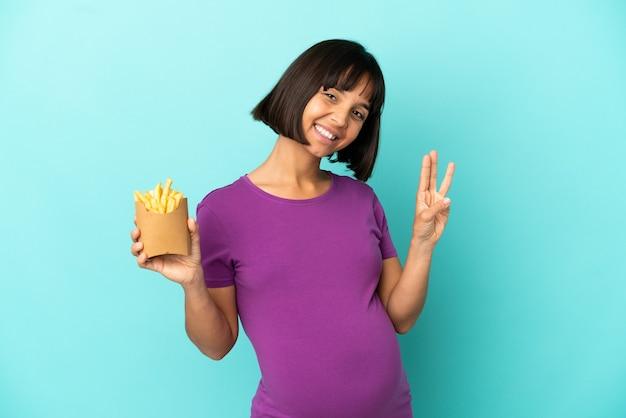 Mulher grávida segurando batatas fritas sobre um fundo isolado feliz e contando três com os dedos