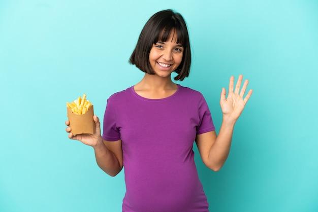 Mulher grávida segurando batatas fritas sobre um fundo isolado saudando com a mão com uma expressão feliz