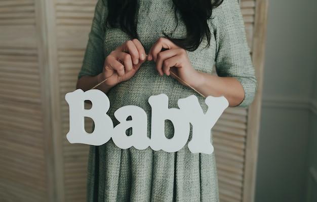 Mulher grávida segurando bebê palavra de madeira. esperando por um bebê. foto de alta qualidade