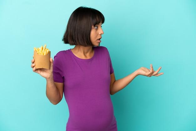 Mulher grávida segurando chips fritos sobre um fundo isolado com expressão de surpresa enquanto olha para o lado