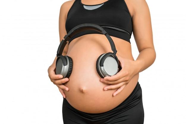 Mulher grávida segurando fones de ouvido na barriga.