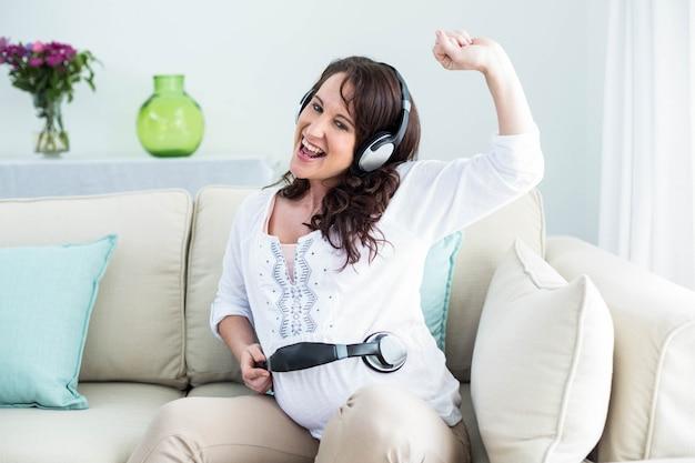 Mulher grávida, segurando, headphone, ligado, barriga, em, sala de estar