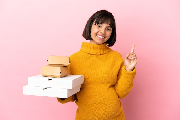Mulher grávida segurando pizzas e hambúrgueres isolados no fundo rosa, mostrando e levantando um dedo em sinal dos melhores