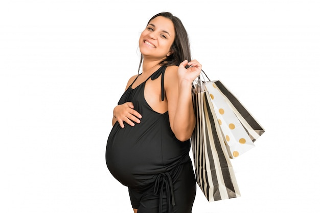 Mulher grávida segurando sacolas de compras
