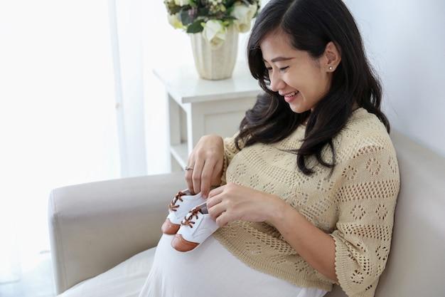 Mulher grávida, segurando, sapatos bebê