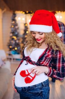 Mulher grávida segurando sapatos de bebê de bruços no fundo da paisagem de ano novo