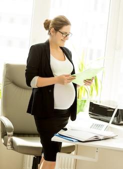 Mulher grávida segurando um arquivo com documentos no escritório