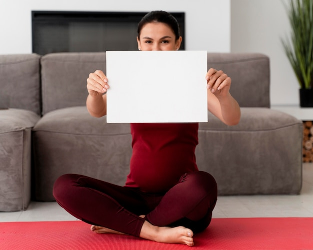 Mulher grávida segurando um cartão branco