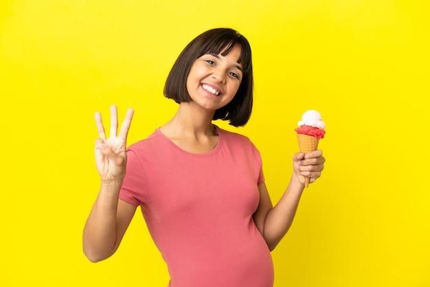 Mulher grávida segurando um sorvete de corneta isolado em um fundo amarelo feliz e contando três com os dedos